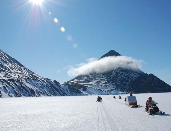 Motoneige dans une vallée enneigée - Canada | Les Mondes Polaires