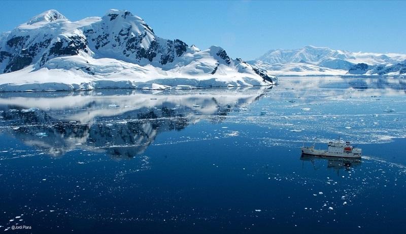 Bateau d'expedition dans une mer de glace et montagnes enneigées - Peninsule Antarctique | Les Mondes Polaires