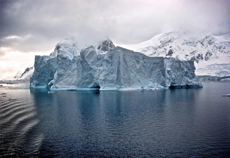 Immense iceberg devant les falaises enneigées - Antarctique | Les Mondes Polaires