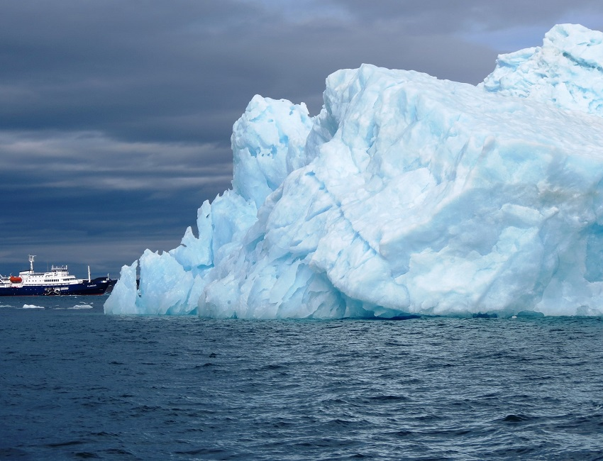Bateau d'expédition devant un immense iceberg - Groenland | Les Mondes Polaires
